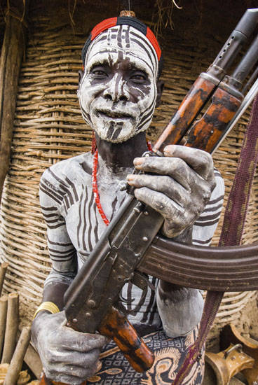 Ethiopia, Lower Omo River Basin, Chelete, a Duss tribal communitiy, man with body and face paint holding AK 47 (Kalashnikov) in front of granary