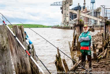 USA: New Jersey, Lower Raritan River Basin, Raritan River Estuary, Sayreville, Portuguese fisherman in front of industrial complex (Reliant Energy, et al) with rods to catch dinner, despite advisories against pollution