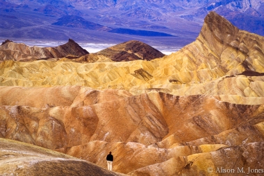 California: Death Valley National Park, view from Zabriskie Point with tourist enjoying overlook, January.