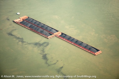 USA:  Louisiana, New Orleans, Lower Mississippi River Basin, flight over coastal wetlands south of New Orleans, aerial view of barge carrying uncovered coal, spilling into the Mississippi River