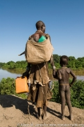 Ethiopia: Omo River Basin, Duss, a Karo tribal village, woman with jugs for water and young son on bank of Omo River