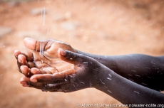 Africa: Kenya; Pokot Land, Lomut, child collecting rainwater from gutter in thunderstorm, a CABESI project