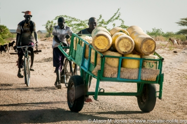 Africa:  Kenya; Turkana Land, man pushing cart of gerry cans to be filled with water from the river outside of town