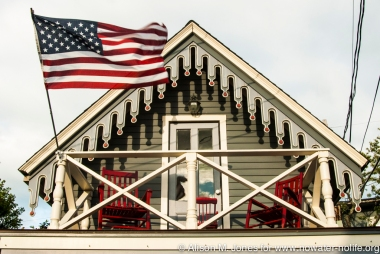 USA:  Massachusetts, Martha's Vineyard, Oak Bluffs, Methodist Campground Victorian architecture, upstairs balcony with flag
