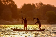 Zambia: Livingston, two men poling dugout canoe across Zambezi River upstream off Victoria Falls