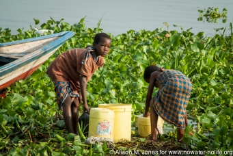 Tanzania: No Water No Life Mara River Expedition, Musoma, Lake Victoria, Nyarusurya Beach Management Unit and fish market, women collecting water in buckets amidst fishing boats and water hyacinth