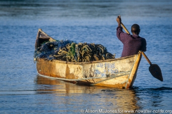 Kenya: Luo fishing village, fisherman paddling boat