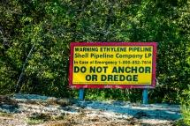 USA: Louisiana, the Atchafalaya Basin, with C. C. Lockwood, Atchafalaya River bank signage for ethylene gas pipeline